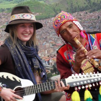 Student playing guitar and native playing flute, Sucre, Bolivia