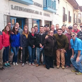 Students posing in front of the old school in Cusco, Peru
