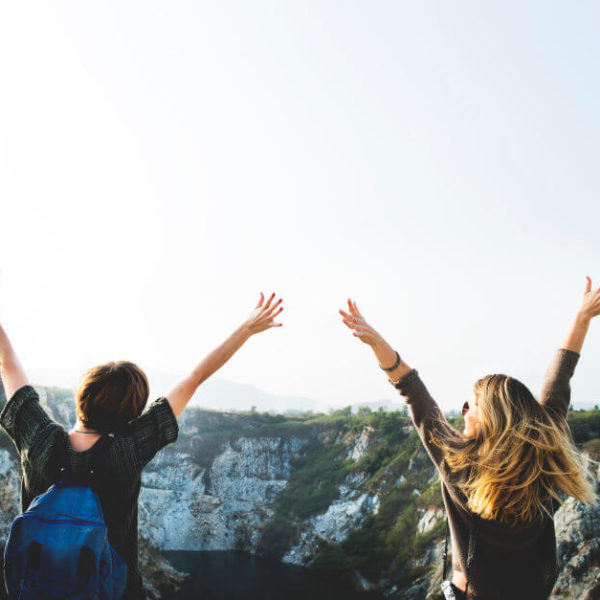 Two friends looking at a mountain and with their hands up